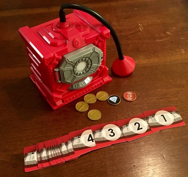 The safe with the stethoscope attached. Coin, jewel, and alarm tokens are laid in front of it beside numbers cards.