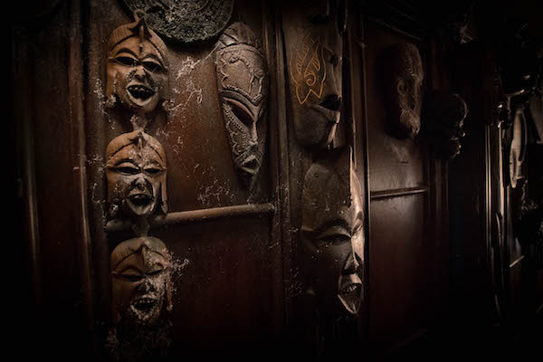 In-game: A wall covered in cobwebbed tribal masks.