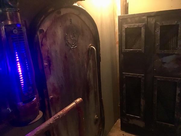 In-game: A metal door beside a tube glowing blue.