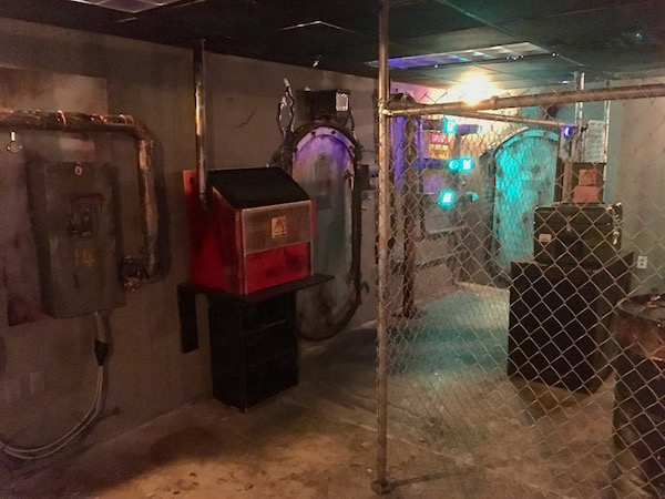 In-game: A wide angle image of the bunker. Doors and interactions lining the walls, a chainlink fence dividing part of the room.