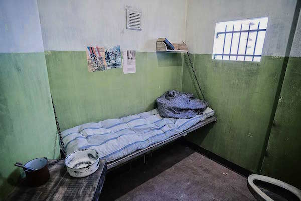 In-game: A prison cell with a small bed, toilet, and table.