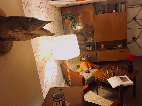 In-game: A drab 1980s living room in East Berlin. A stuffed fish named Erich hangs on the wall.