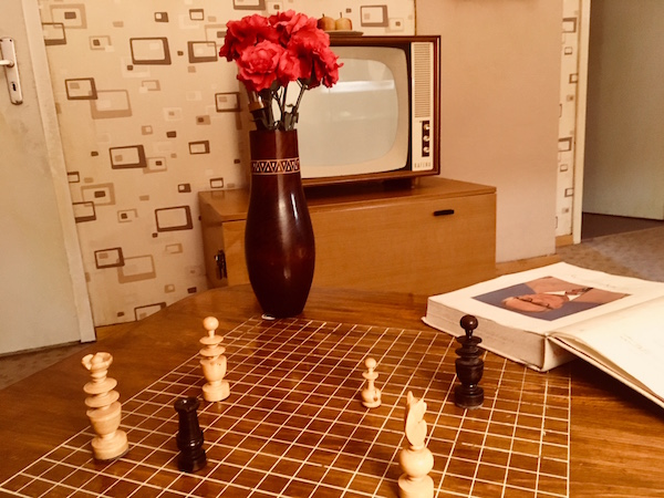 In-game: A gridded cocktail table with chess pieces on it, and a large 1980s television set in the distance.