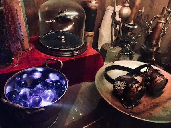 In-game: an assortment of steam punkish items, the Philosopher's Stone, and a glowing bowl of purple orbs.