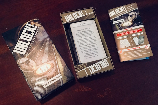 The opened box for Unlock! The Formula. The deck of cards rests in the box the instructions beside it.