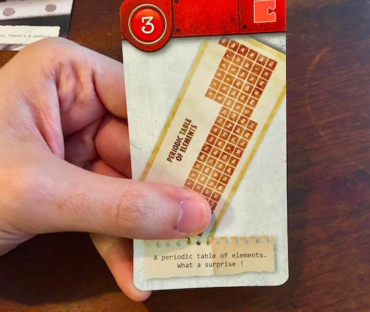 """Red card depicting a periodic table of elements. The flavor text reads, """"A periodic table of elements. What a surprise!"""""""