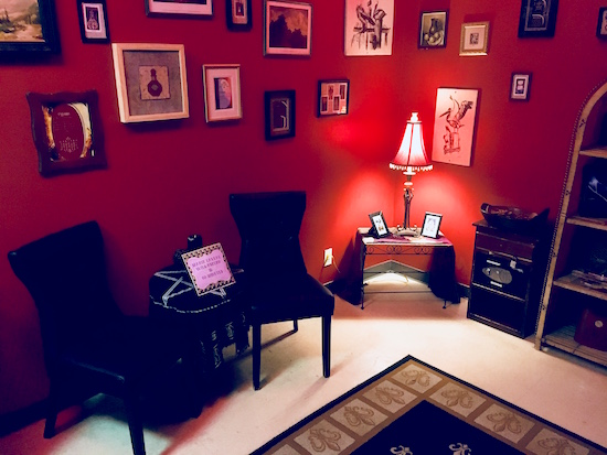 In-game: A livingroom space with two chairs, a small table with a light, and red walls with many pictures hung from it.