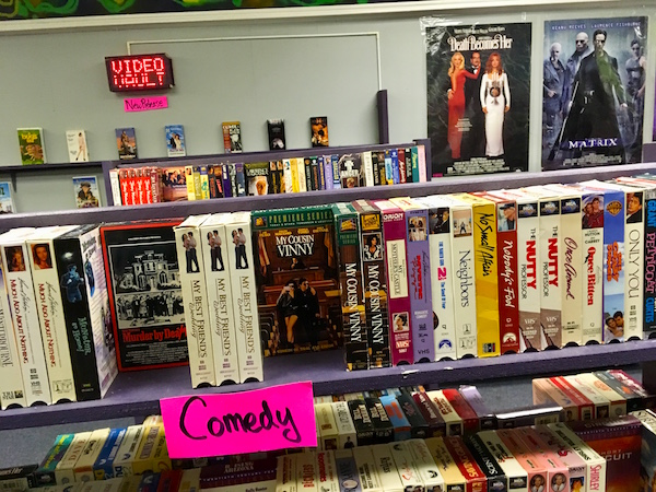 In-game: The comedy section of a video rental store. Murder By Death and My Cousin Vinny are clearly staged.