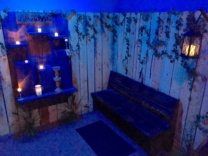 In-game: A dim, fenced-in yard with a candle-lit shrine for offerings.