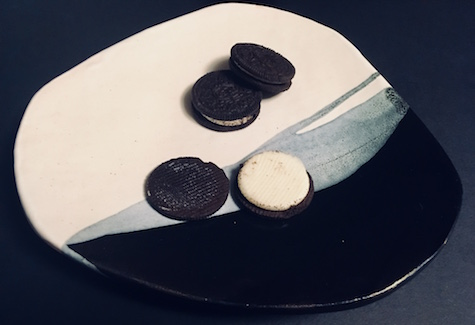 3 mystery Oreos laid on a black and white plate. One of the Oreos has been twisted open.