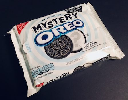 White packaging for Mystery Oreo cookies. There is an opened Oreo with a question mark engraved in the cream.