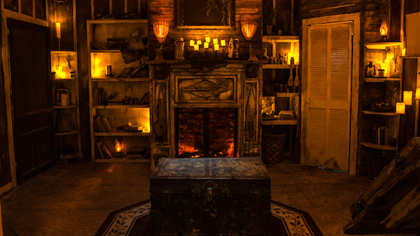 In-game: An old, dramatically lit house on the bayou. A locked truck sits in the center of the room with a glowing fireplace and lit candles in the background.