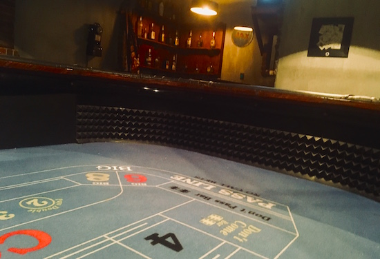 In-game: shot from within a craps table, the casino's bar lit in the background.
