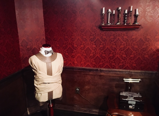 A straight jacket is affixed around a bow tied mannequin.