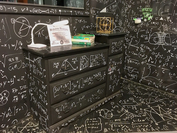 In-game: Black walls and furniture covered in white writing of mathematical symbols and equations.