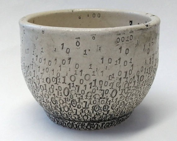 A while ceramic cup with black 1s and 0s imprinted all over.