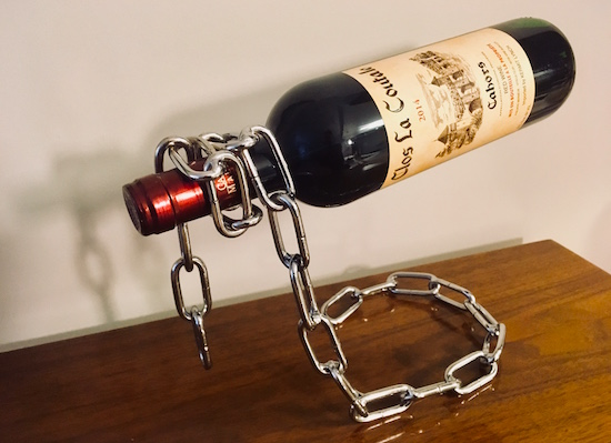 A chain standing upright, magically floating a bottle of wine.