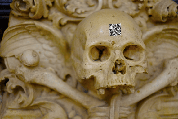 An intricate and old skull statue with a QR code on the forehead of the skull.