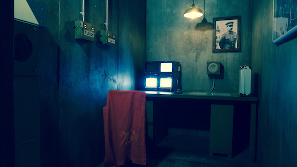 In-game: A concrete Soviet bunker with concrete walls, a PA system, and a photo of Stalin hanging on the wall.