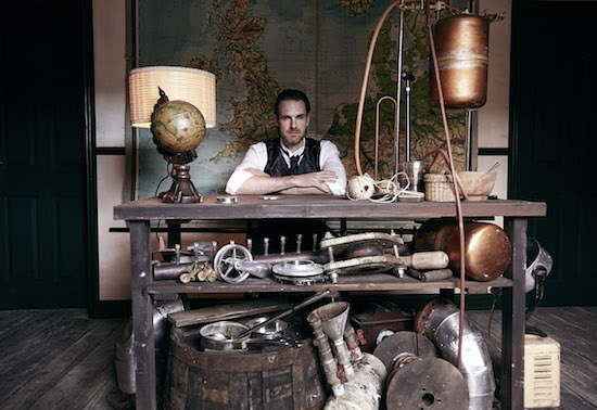 A steampunk office with a map of England and a massive collection of metal and wooden parts.