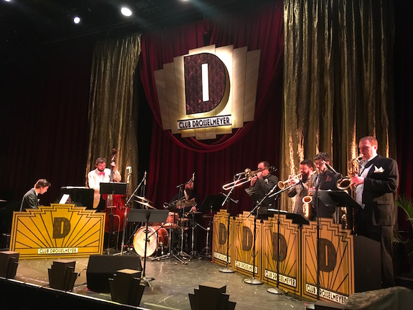 The red and gold Club Drosselmeyer stage with a 7 piece jazz band playing.