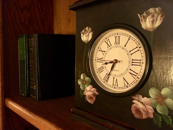 In-game: Close up of a clock on a bookcase.