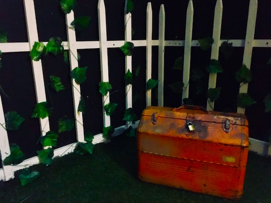 In-game: A front yard at night. A locked red toolbox sits in front of an ivy covered white picket fence.