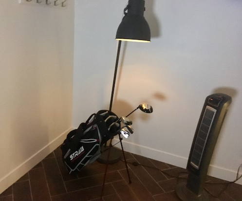 In-game: A bare bones room with a lamp illuminating a golf bag and an air purifier.