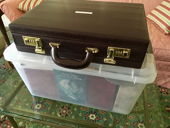 A locked brief case sitting on a large plastic crate in a hotel room.