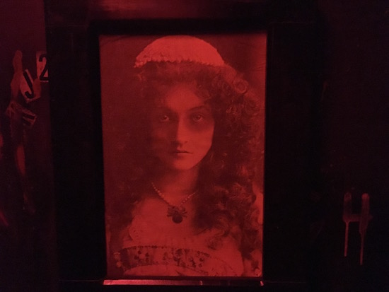 In-game: a hanging red and black portrait of a woman.