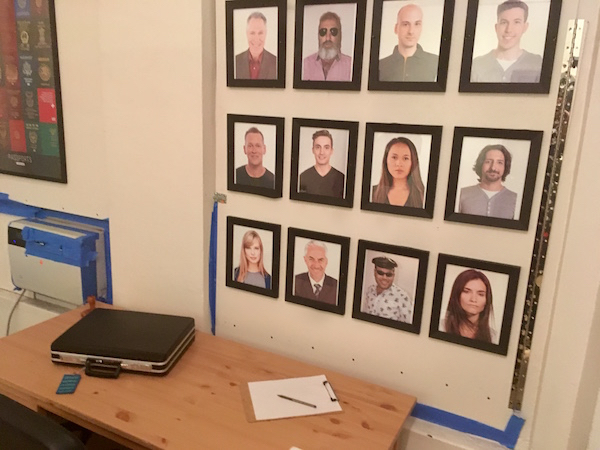In-game: A black suitcase on a desk, the wall behind has 12 portraits of different people.