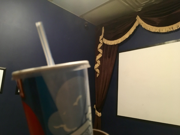 In-game: The screen of a movie theater in the background, a cup and straw in the foreground.