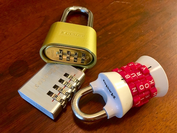 Three Master Lock letter locks with the combinations entered as sand, star, and bury.