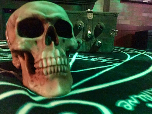 In-game: A skull on a strange table with a book covered in protruding eyeballs behind it.