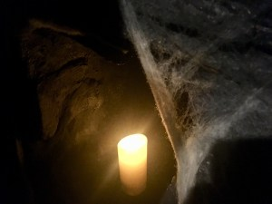 In-game: A dark cave with cobwebs and a glowing candle.