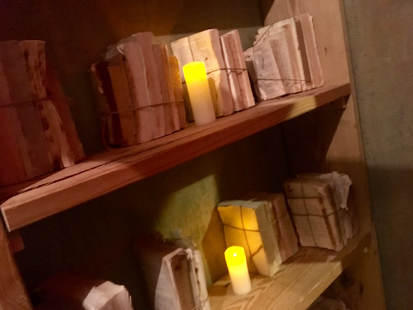 In-game: A wooden bookshelf covered in roped bundles of coverless books and glowing candles.