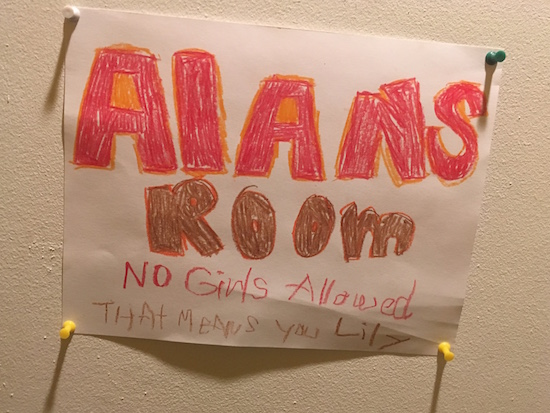 "In-game: a paper sign tacked to a door that reads, ""Alans room: no girls allowed that means you Lily."""