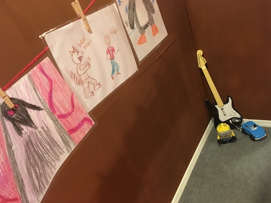 In-game: a string of child's art held up by clothespins, hanging over some kids toys.