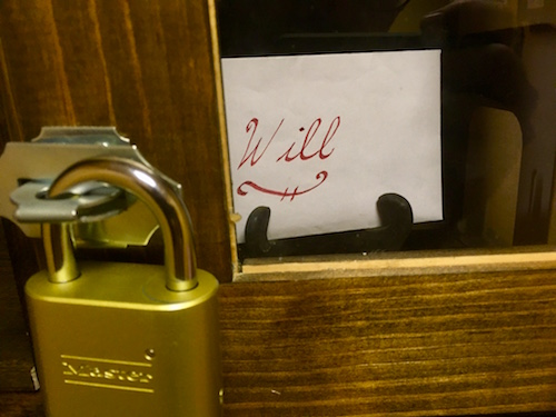 In-game: the will locked in a transparent box sealed shut with a padlock.