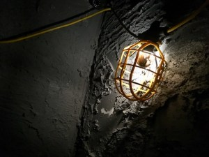 In-game: close up of a caged light hung in a dark dig site.