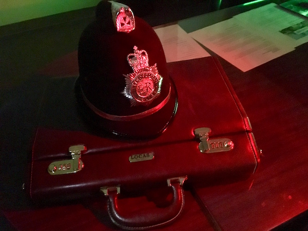 In-game: a police hat and attaché case on a desk.