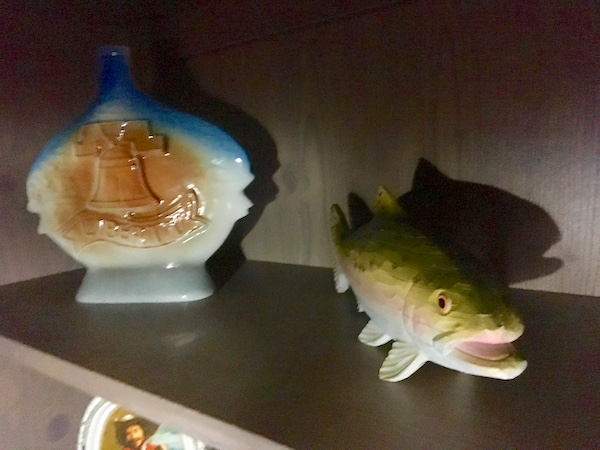 In-game: Ceramic bottles and a fish in a dim room.
