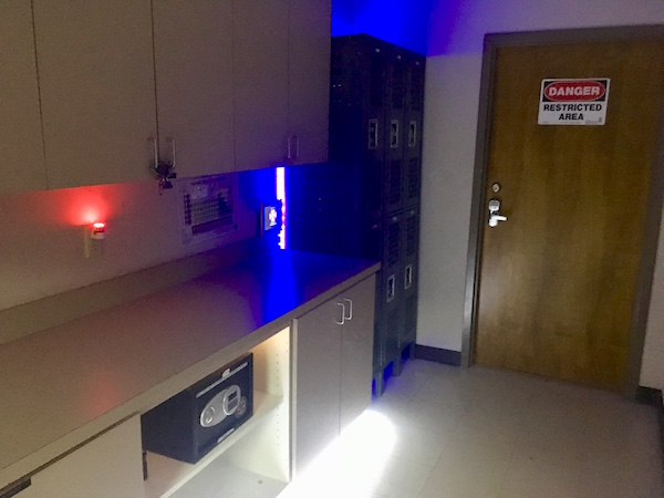 In-game: A lab environment with lockers and lights glowing red and blue.
