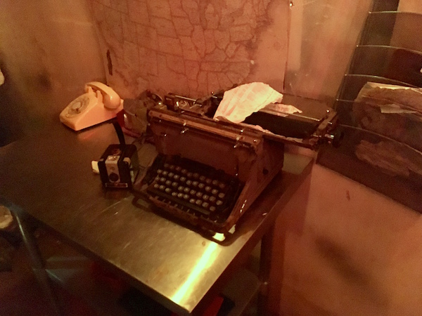 In-game: An old broken typewriter on a desk beside a Brownie camera, and rotary phone.