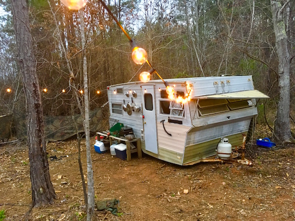 In-game: An old trailer in the middle of the woods. It's lit with a long strand of light bulbs.