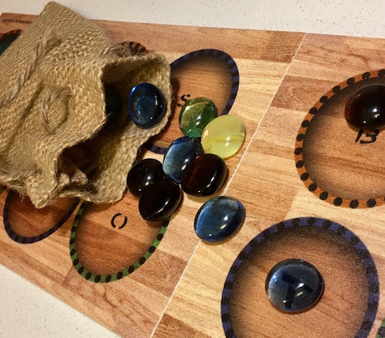 The Mancala board with glass beads and a burlap bag to hold them.