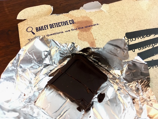 Chocolate resting atop an envelope from the Bailey Detective Company.