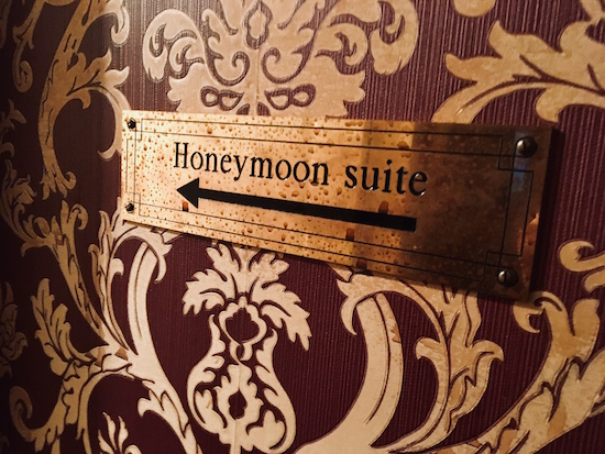 "In-game: Closeup of a bloodied sign pointing towards the ""Honeymoon suite."""