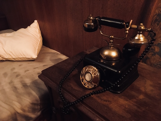 In-game: an old telephone beside a tossed bed.