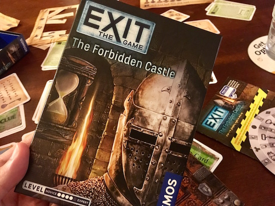 Exit The Game: The Forbidden Castle box being held over assorted game components.